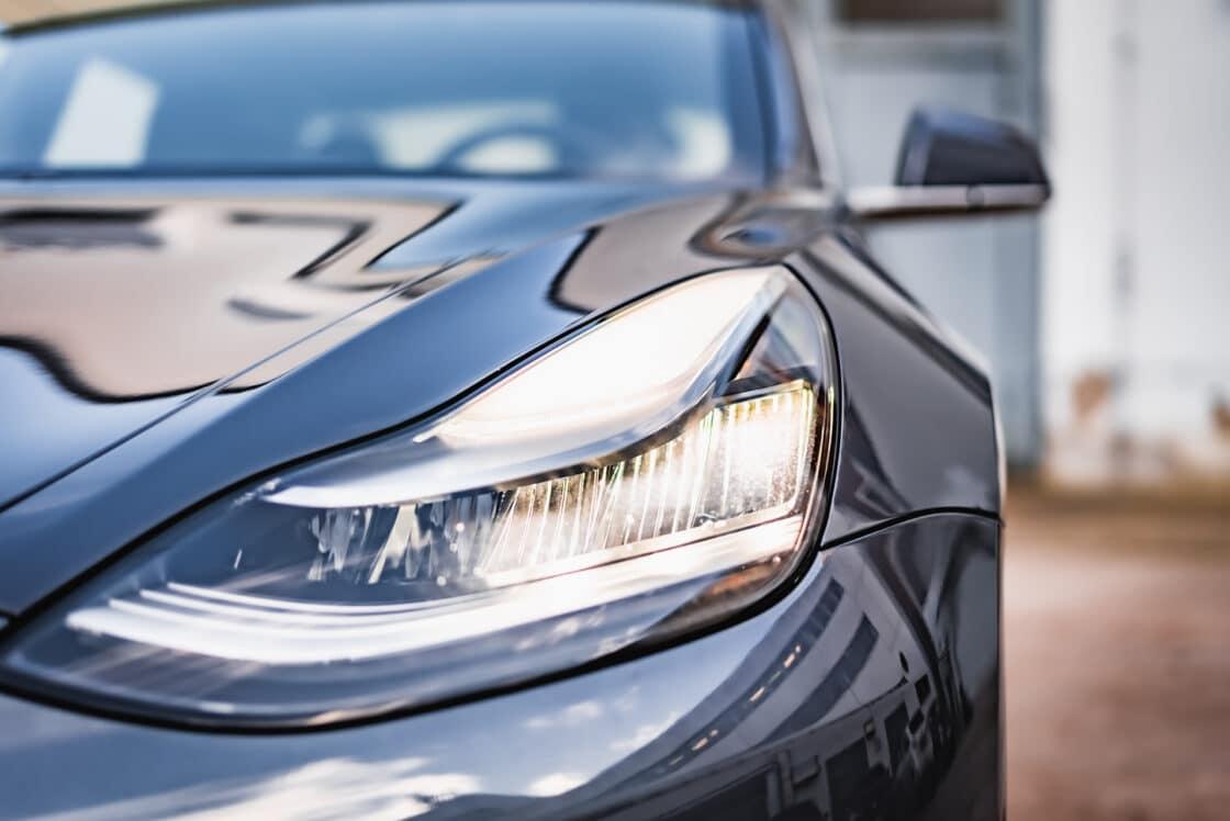 Zu sehen ist der Scheinwerfer des Tesla Model 3