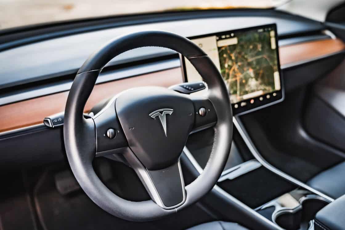 Zu sehen ist das Lenkrad und das Infotainment-Display des Tesla Model 3