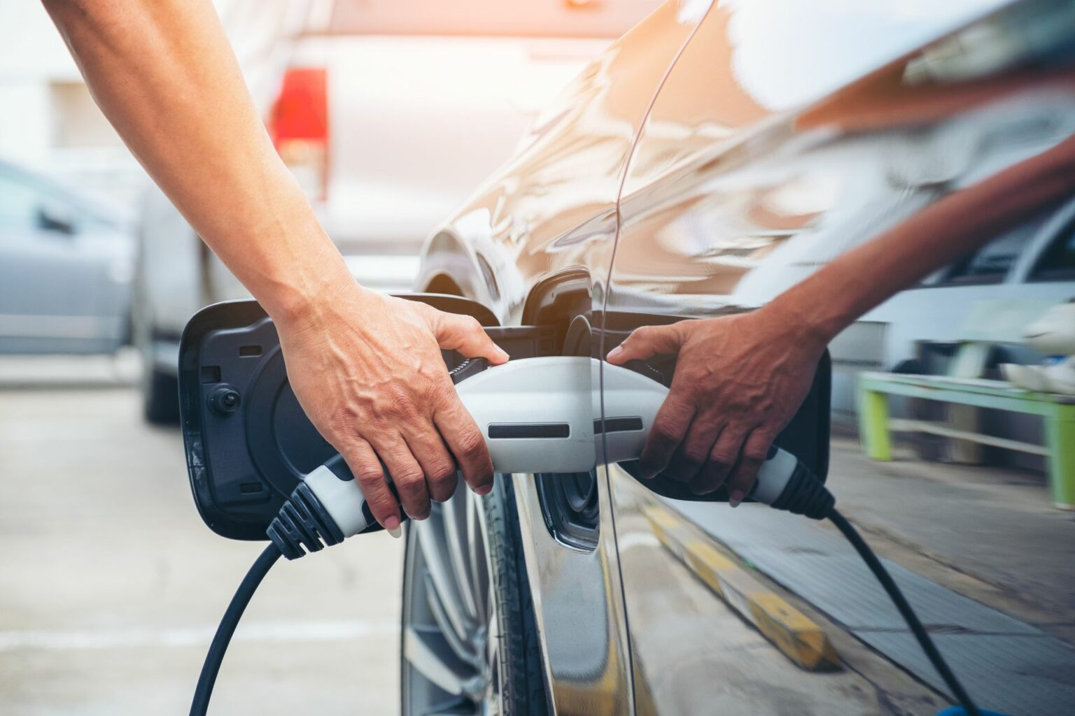 Eine Hand steckt einen Stromstecker in ein Elektroauto