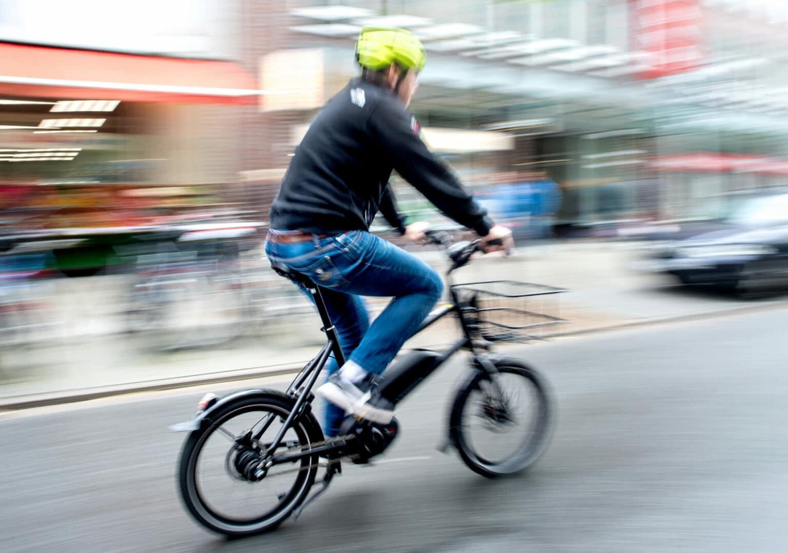 Fahrer eines E-Bikes fährt mit hoher Geschwindigkeit durch eine Straße