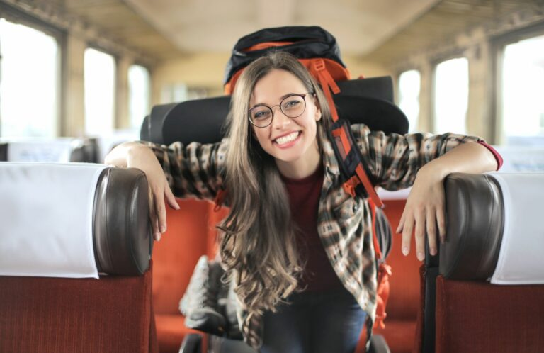 Enthusiast girl traveling by train with a big backpack
