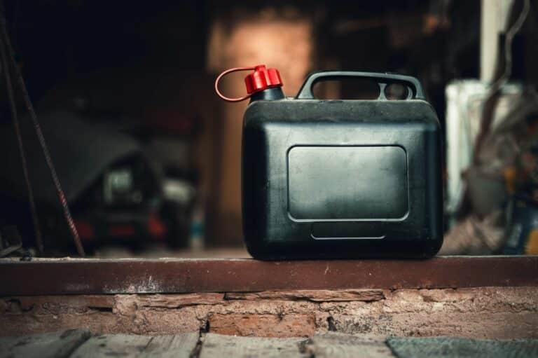 Ein alter schwarzer Reservekanister steht in einer dreckigen Garage