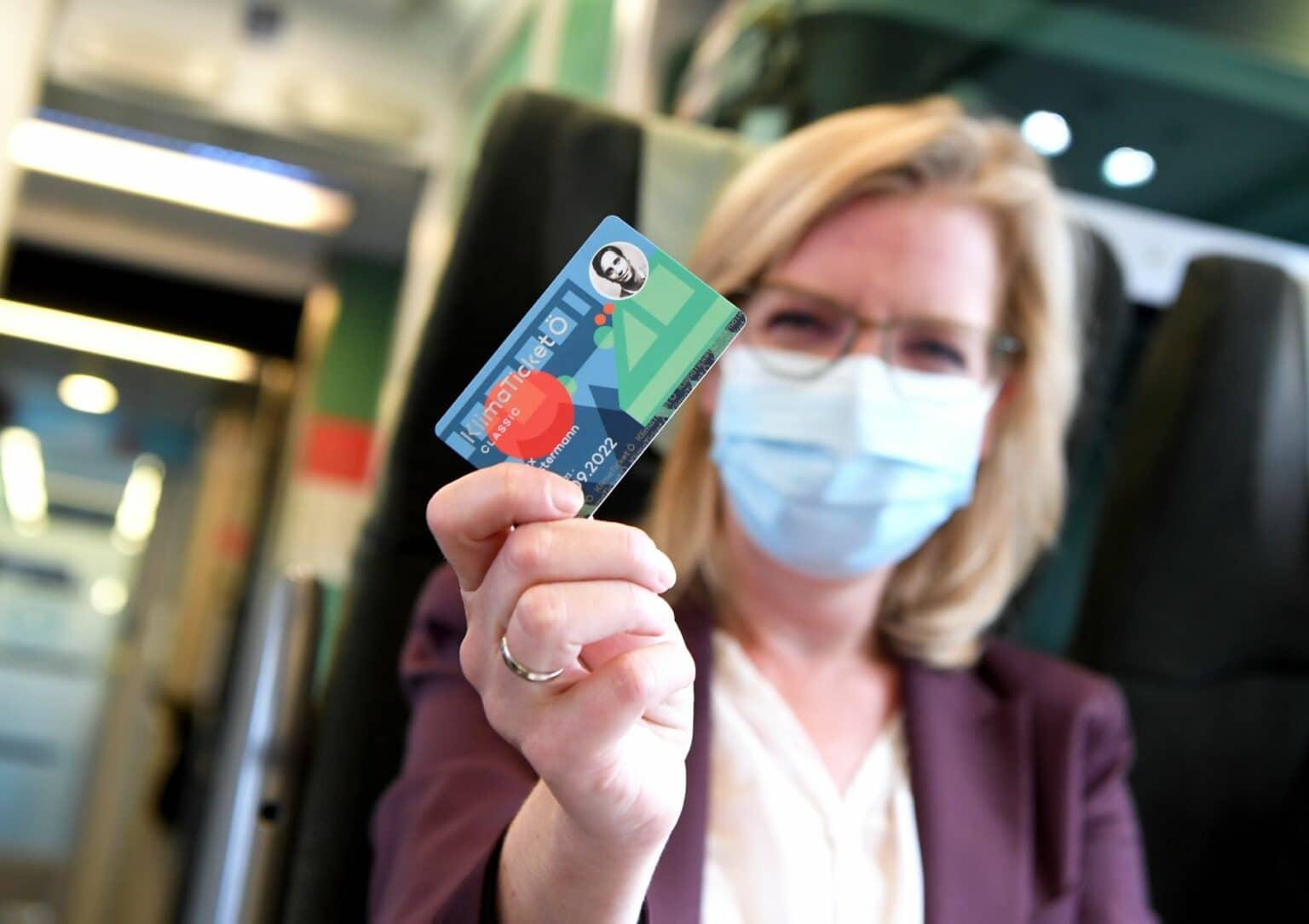Eine Frau sitzt in einem Zug und hält ihr Zugticket in die Kamera