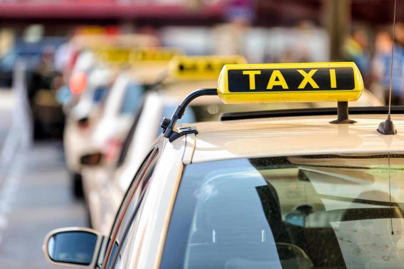 Mehrere Taxis stehen aufgereiht an einem Taxi-Stand
