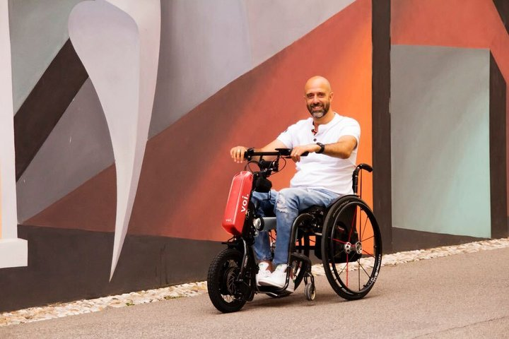 Mann im Rollstuhl bedient eine Antriebseinheit für manuelle Rollstühle